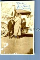 FOUND B&W PHOTO U_9567 WOMAN IN DRESS POSED WITH KIDS ON SIDE OF OLD CAR