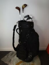 full size black golf bag with some clubs and masters umbrella
