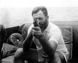 ERNEST HEMINGWAY HOLDING A TOMMY GUN, CIRCA 1935 - 8X10 PHOTO (OP-689)