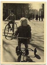 Petite fille sur vélo tricycle ville rue - photo ancienne an. 1950