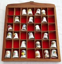 COLLECTION OF THIMBLES IN DISPLAY CASE.
