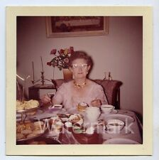 1960s  Square color snapshot Photo Lady at dinner table coffee and snacks