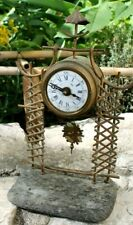 petite et ancienne  pendulette ou réveil avec son balancier en forme de soleil