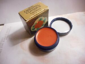 Avon Oriental Classic Lip Gloss in a round container with flowers,coral/peach