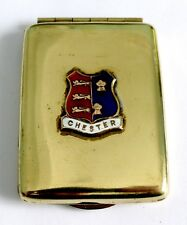 AN ART DECO BRASS MATCH BOOK CASE WITH CHESTER ENAMEL PLAQUE