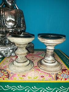 A PAIR OF CHUNKY INDIAN DISTRESSED WOODEN CANDLESTICKS