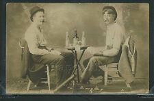 SD Hurley RPPC 1908 STUDIO CARNIVAL PHOTO 2 MUSICIANS PLAYING CARDS Drink BOOZE