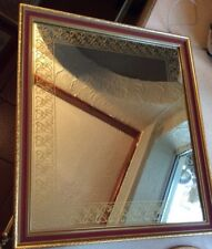 A GOLD FRAMED WALL MIRROR WITH A DARK RED BOARDER ALSO A GOLD PATERN # D