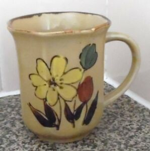 LIGHT BROWN MUG CUP WITH FLORAL DESIGN MARKED FOREIGN UNDERNEATH