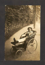 REAL-PHOTO POSTCARD:  YOUNG BOY SITTING IN ROLLING CHAIR - PROBABLY IN FLORIDA ?