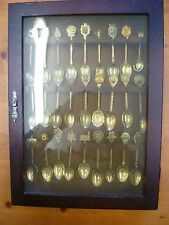 COLLECTION OF 27 SOUVENIR SPOONS, FROM THE UK & ABROAD, IN A WOODEN DISPLAY CASE