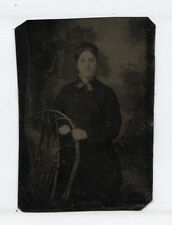 TINTYPE WOMAN GRIPPING WICKER CHAIR BACK. PAINTED BACKGROUND.