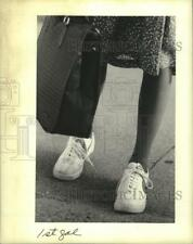 1993 Press Photo Trading in high heel pumps for sneakers on walk home