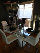 Glass dining room table with 4 white leather chairs
