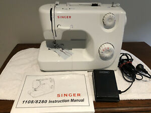 Portable electric white Singer sewing machine in excellent condition.