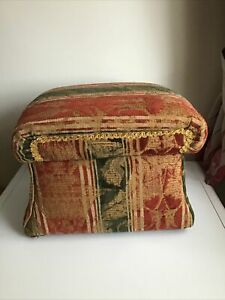 A SMALL UNUSUAL SHAPED MATERIAL COVERED FOOT STOOL WITH STORAGE