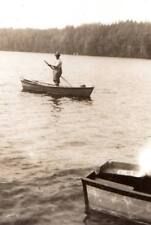vintage snapshot image of man fishing leaving problems behind boats reflections