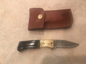Damascus folding blade knife w/black horn handle, etched brass & leather case
