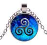 Collier pendentif symbole triskel spirales, fond bleu.