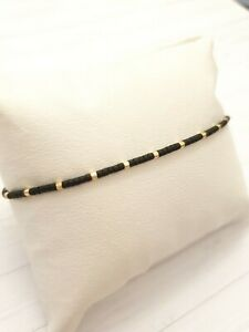 Tiny delicate bracelet Layering beaded black and gold.