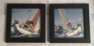 A pair of sailing pictures in black wooden frames.