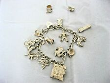 Vintage solid silver charm bracelet with 15 charms .