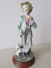 CONTINENTAL BOY FIGURINE WITH PUPPY, SIGNED.