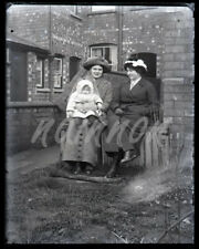 Glass negative -TWO WOMEN with BABY seated in back yard - all warmly dressed.