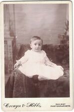 Cabinet Photo of Baby in long White Dress, Large Eyes. Card says Railway Photog.