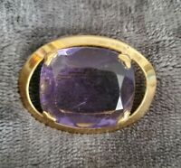 Vintage gold tone oval brooch with large purple glass stone claw