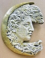 Half moon with a profile of a woman hair flowing in the Art Nouveau style