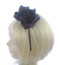 Black open rose flower fascinator on a band