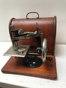 Vintage lead child's hand crank mini sewing machine with wooden Brentwood dome c