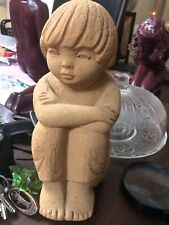 Stone sculpture of a child seated wisely