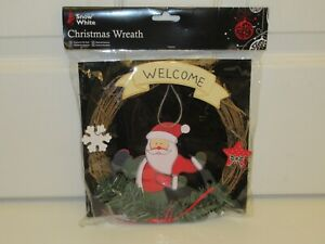 Wicker Christmas wreath with little wooden Santa and 'Welcome' sign