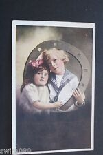 Vintage 1922 postcard with boy in sailor suit, girl and horseshoe.