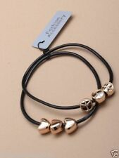 Card of 2 black gummy bangles with gilt peace or heart charms  (k1)