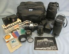 OLYMPUS OM10 35MM SLR CAMERA OUTFIT WITH THREE LENSES, FLASH, EXTRAS & CASES.