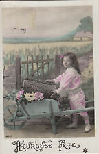 CI64.Vintage Greetings Postcard.Girl pushing logs in a wheelbarrow.