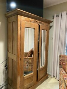 ANTIQUE OAK ARMOIRE with shelves and beveled glass mirrored doors