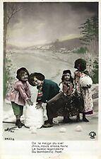 Kinder bauen einen Schneemann, um 1910