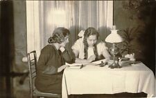 TWO GIRLS SIT AT THE TABLE IN LEAVING ROOM & VINTAGE OCCUPATIONAL PHOTO POSTCARD