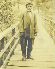 RPPC: Dapper YOUNG Black AFRICAN AMERICAN MAN in HAT & ILL-FITTING SUIT on BRIDG