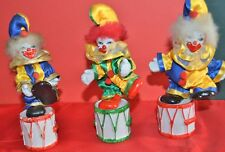 THREE CLOWNS STANDING ON DRUMS