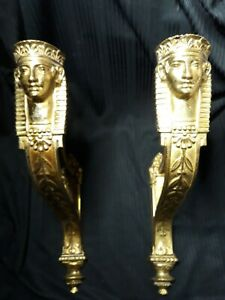 A pair of French Empire bronze dore curtain rod holder brackets