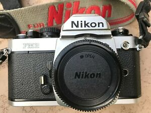 Nikon FM2 35mm film camera body collectible, bag, flash light, one roll of film