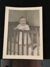 Child Baby in Crib Holding Railing Wearing Dress Smiling Smile