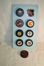 Eight 1960's NHL Approved Official Team Pucks w/Puckolector Display
