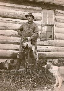 8x10 repro photo: Hunter boots rain gear birds rifle dog rustic log cabin 1912