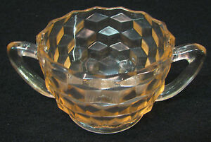 Pink depression glass sugar bowl with ruffled rim and two handles diamond design